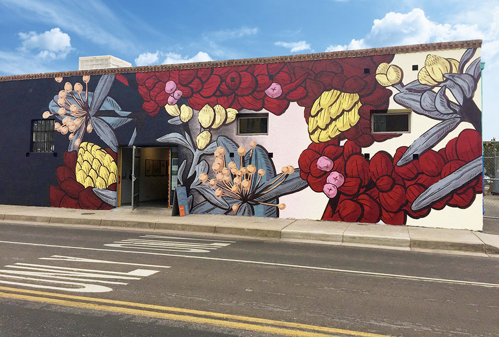 Photo of the muraists large botanical painting on the side of a building.