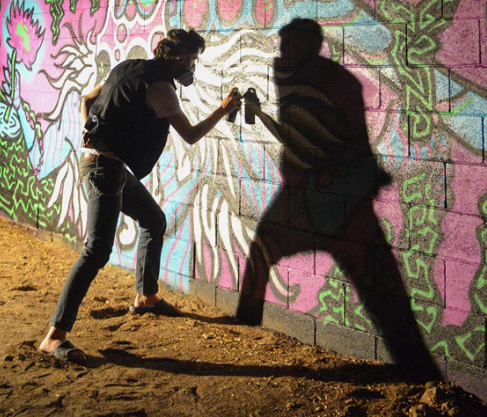 dramatic photo of the artist spray painting a wall in the dark of the night. his shadow is cast.
