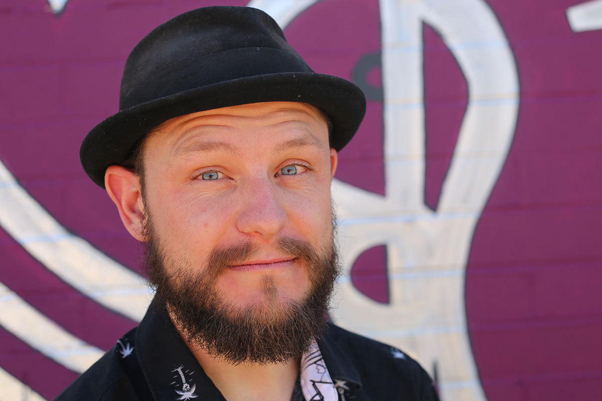 Photo of the blue eyed, bearded artist in a hat looking at camera smiling.