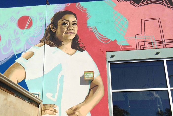 A large mural of a powerful looking confident woman.