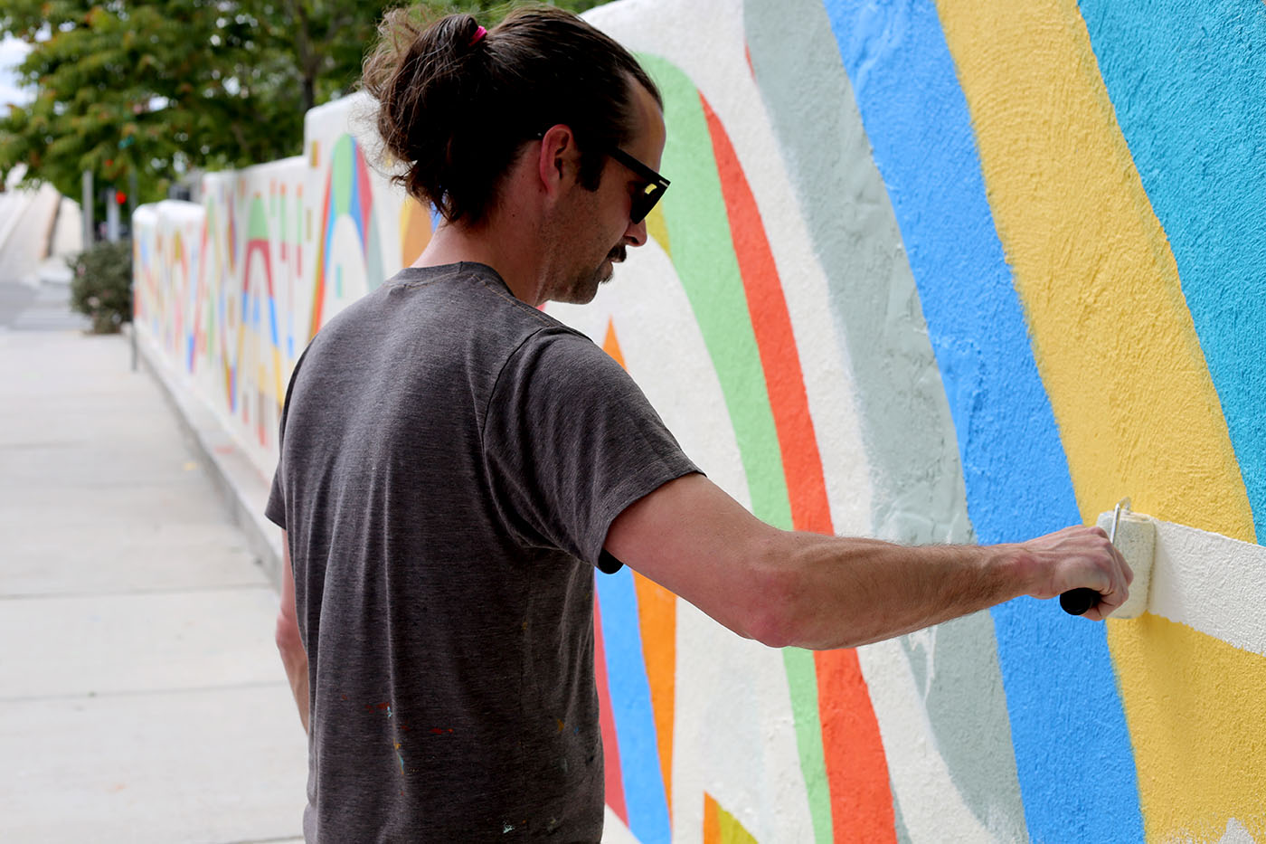Photo of the pony-tailed artist in sunglasses painting a mural in progress.