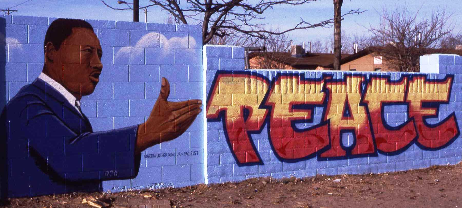 hand gesturing toward lettering painted on wall