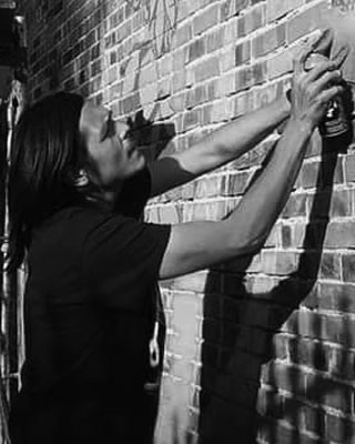 man spray painting wall
