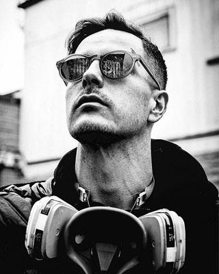 man wearing sunglasses and gas mask around neck